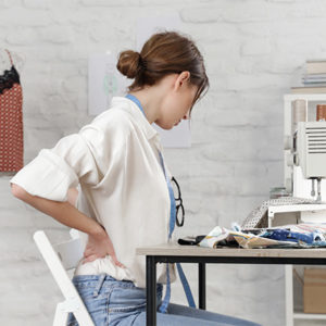 Woman with back pain sewing on sewing machine in small studio, f